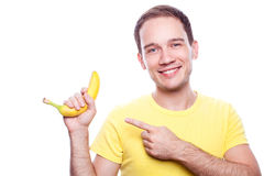 Smiling boy points to banana. Smiling handsome guy holding yellow banana and pointing to it over white background. healthcare concept. studio shot Stock Images