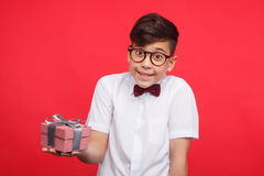Smiling boy posing with giftbox. Adorable kid in glasses standing with small giftbox on red background and looking at camera stock photography