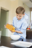 Smiling boy pouring corn flakes in bowl at home Royalty Free Stock Images