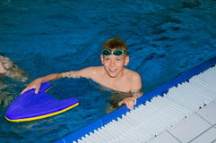 Smiling boy is practicing in the pool stock photos