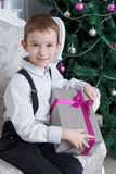 Smiling boy with present under Christmas tree Stock Images