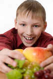 Smiling boy pulls himself to the fruit Stock Images