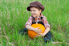 Smiling boy with pumpkin on the grass. Smiling boy with big yellow pumpkin in hands sitting on the grass Royalty Free Stock Photography