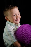 Smiling boy with purple rubber ball. A smiling boy holds a purple rubber ball on a black background Stock Images