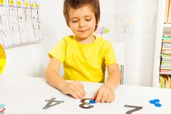 Smiling boy put coins on numbers learning count Royalty Free Stock Image