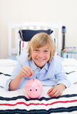 Smiling boy putting coins in a piggybank Stock Photos