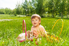 Smiling boy with rabbit and baskets on the grass Stock Images