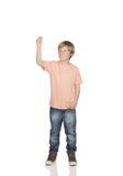Smiling boy raising his arm holding something Stock Images