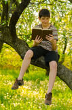 Smiling boy reading book in the nature Stock Image