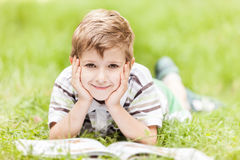 Smiling boy reading book outdoor Stock Photo