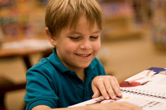Smiling boy reads a book at libary. A cute, smiling seven year old boy reads a book at the library or book store.  He has light brown hair and wears a turquoise Royalty Free Stock Images