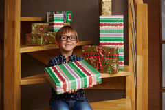 Smiling boy ready to open Christmas presents Stock Photos