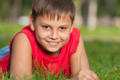 Smiling boy in red on the grass Stock Photos