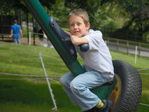 Smiling boy resting on large spin-swing. Day out at playground in park: portrait of a happy boy sitting on a spin-swing, resting and smiling royalty free stock image