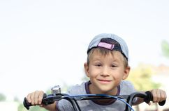 856550f7c23 Smiling boy riding bicycle. Little smiling boy riding bicycle in city park  royalty free stock