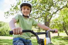 Smiling boy riding bicycle at park Royalty Free Stock Photo