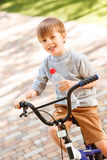 Smiling boy riding bike with bottle of water Royalty Free Stock Photo