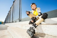 Smiling boy in roller blades sitting on the stairs Stock Images