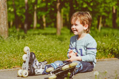 Smiling boy in rollers sits on walkway at park Royalty Free Stock Photo
