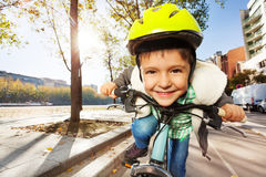 Smiling boy in safety helmet riding his bike. Close-up portrait of cute smiling boy in yellow safety helmet riding his bike at sunny day Royalty Free Stock Images