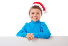 Smiling boy in Santa hat with empty banner Royalty Free Stock Photos