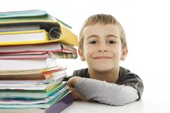 Smiling boy with school books on the table Stock Photos
