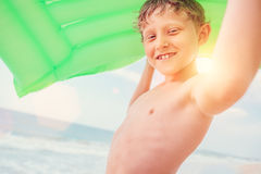 Smiling boy sea portrait with green air swiming mattress Royalty Free Stock Images