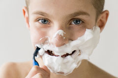 Smiling Boy Shaving Face with Plastic Razor Royalty Free Stock Photos