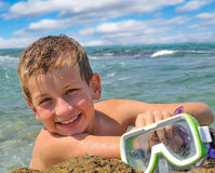 Smiling boy on the shore holds a mask for diving Royalty Free Stock Photography