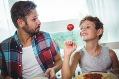 Smiling boy showing a cherry tomato to his father royalty free stock image