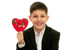 Smiling boy is showing red heart with flowers on Royalty Free Stock Photos