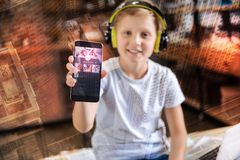 Smiling boy showing a screen of his smartphone while listening to music. Showing screen. Cheerful smiling boy sitting and showing a modern smartphone while Stock Images