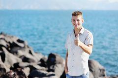 Smiling boy showing thumb up on sea background Stock Images