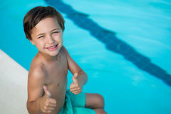 Smiling boy showing thumbs up at poolside. Portrait of smiling boy showing thumbs up at poolside Royalty Free Stock Photo