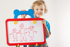 Smiling boy shows his family painted on whiteboard Stock Photo