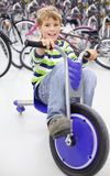 Smiling boy sits on blue tricycle Royalty Free Stock Image