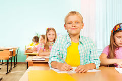Smiling boy sits in class and holds pen to write. Smiling boy sits in class with group of mates holding pen to write in exercise book with other pupils in school Stock Image