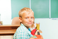 Smiling boy sits at desk with blackboard behind Royalty Free Stock Images