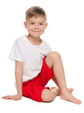 Smiling boy sits on the floor Stock Photo