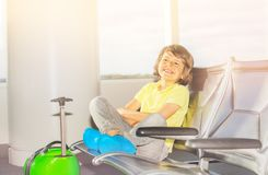 Boy sits in departure terminal waiting for flight stock image