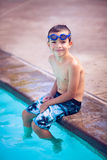 Smiling boy sitting along the pool Stock Photo
