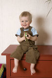 Smiling boy sitting on bureau Stock Images