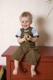 smiling boy sitting on bureau Stock Images
