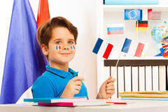 Smiling boy sitting at desk holding French flags Stock Photos