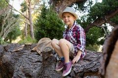Smiling boy sitting on the fallen tree trunk. Portrait of smiling boy sitting on the fallen tree trunk Stock Photos