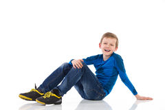 Smiling boy sitting on the floor. Royalty Free Stock Photo