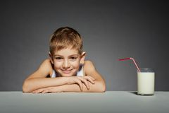 Smiling boy sitting with glass of milk Royalty Free Stock Photos