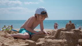 Smiling boy sitting and play with sand on the beach