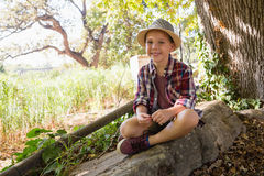 Smiling boy sitting on the rock in the forest Stock Photos