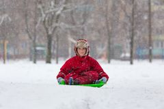 Smiling boy sitting at slide on snowy landscape Stock Photography